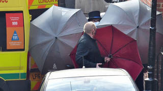 Staff and police hid the occupant of an ambulance using umbrellas amidst a larger police presence.