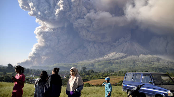People stand and look at the erupting Indonesian volcano