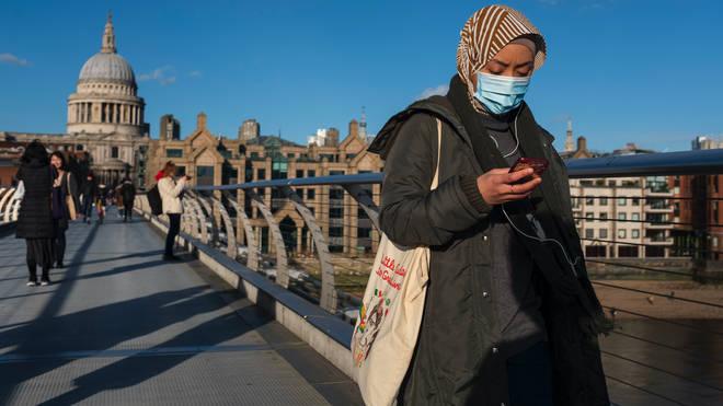 A pedestrian wearing a mask crosses the Millennium Bridge in London