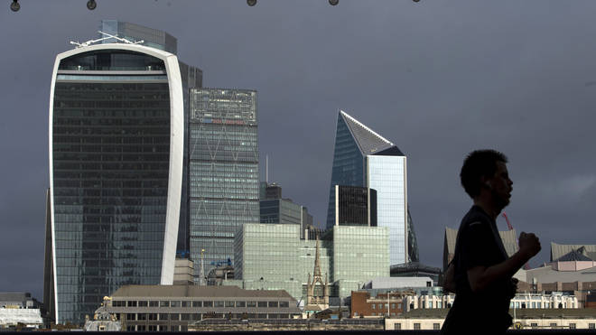A person jogs along the riverside path past the City of London skyline
