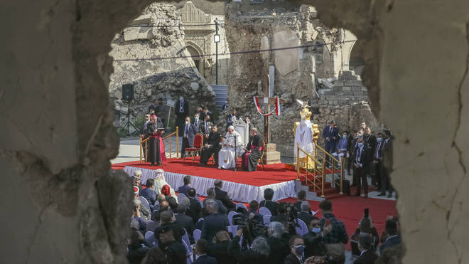 Pope Francis surrounded by shells of destroyed churches