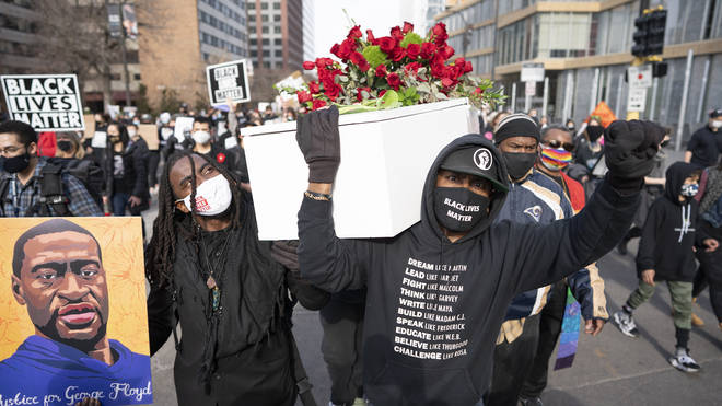 Cortez Rice, left, a friend of George Floyd, and Raj Sethuraju carried a mock coffin to mourn the death of George Floyd during a rally in Minneapolis, Minnesota