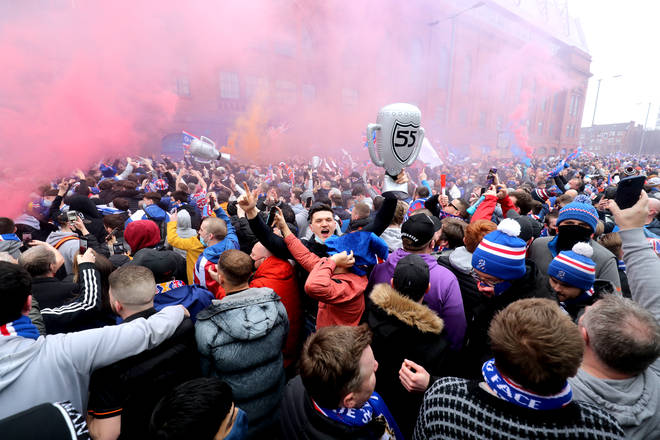 Rangers fans celebrate outside of the Ibrox Stadium