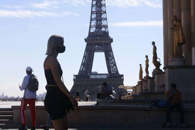 A tourist visits Paris wearing a protective face covering.