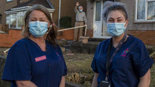 Community Care workers Vivienne Jenkins and Chantelle Healy leave a house after providing social care in Blackwood, Wales.