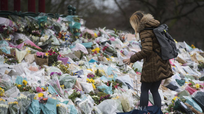 A woman lays flowers at the bandstand in Clapham Common, London, for Sarah Everard