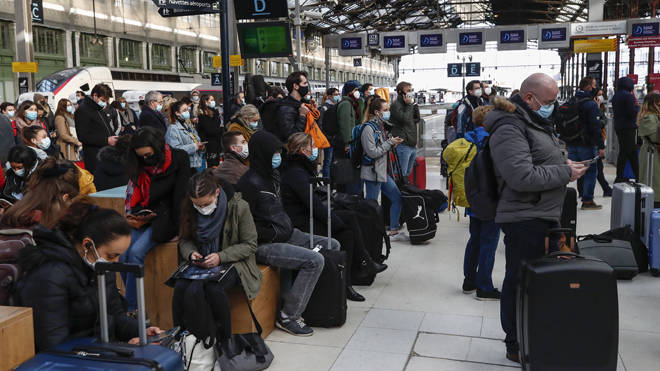 People wait to leave Paris at Gare de Lyon station as the new lockdown came into effect