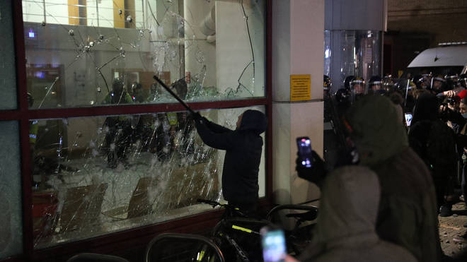 A protester smashes a Bridewell Police Station window