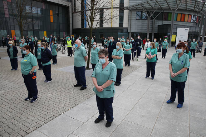 Staff observe a minute's silence outside the Queen Elizabeth University Hospital in Glasgow, during the National Day of Reflection