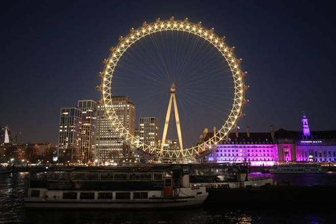 The London Eye in London is illuminated yellow during the National Day of Reflection.