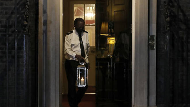 "The doorman of 10 Downing Street carries a candle to signify a ""beacon of remembrance""."