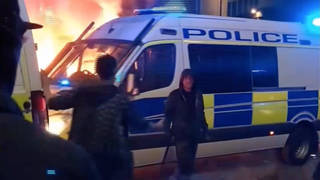 This is the moment an individual appears to attempt to place a lit item under a police van