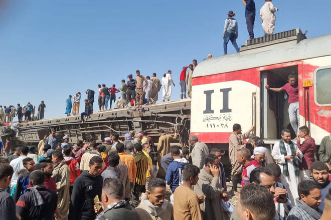 People gather to inspect damaged train cars after two passenger trains collided