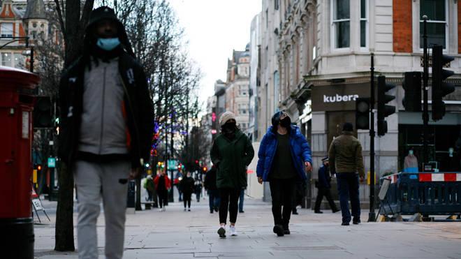 People wearing face masks walk along a near-deserted Oxford Street in London