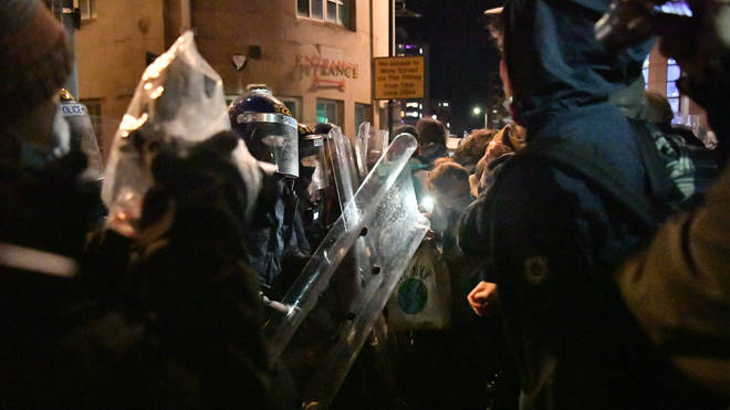 Police with riot shields clash with protesters in Bristol