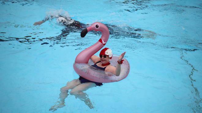 A lido user enjoys a swim with an inflatable flamingo.