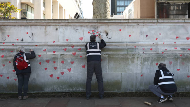 Members of bereaved families paint red hearts on the COVID-19 Memorial Wall opposite the Houses of Parliament at Embankment