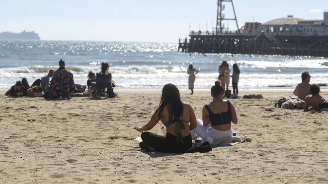 Beach-goers gather in Bournemouth to soak in some sun by the sea.