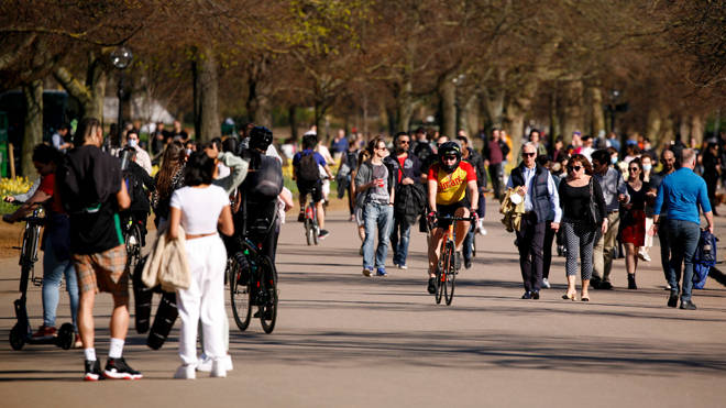 People walk and ride beside in warm spring sunshine beside the Serpentine in Hyde Park as England's lockdown eases