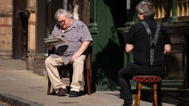 A man reads a newspaper in the sun in Central London