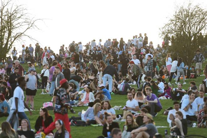 People enjoy the evening sunlight on Primrose Hill