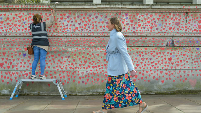 A volunteer paints red hearts on the National Covid Memorial Wall in London. The National Covid Memorial Wall in London