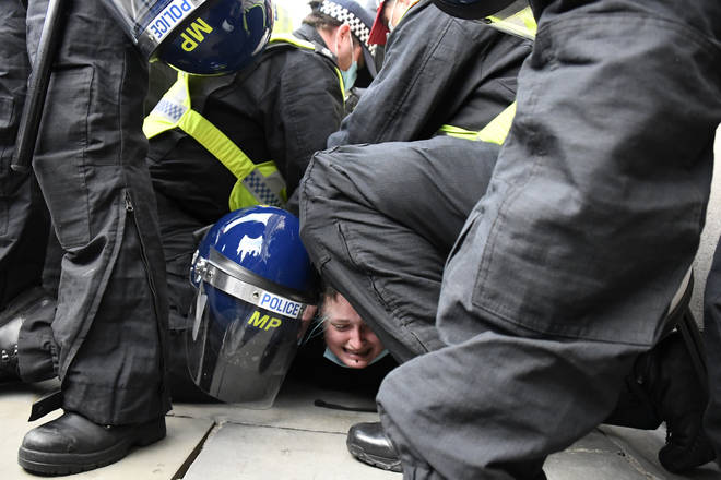Police restrain a demonstrator during clashes following a 'Kill the Bill' protest.