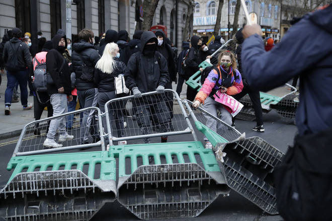 Demonstrators drag road works fences into the street during clashes with police.