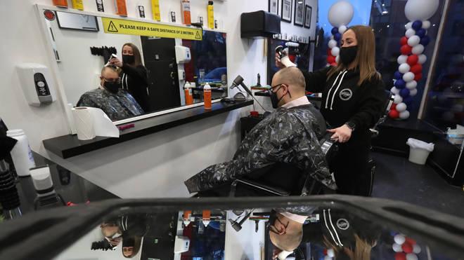 Barber Maggie McGillivray trims Sam Rosenblom's hair at Tony Mann's Barber Shop in Giffnock near Glasgow