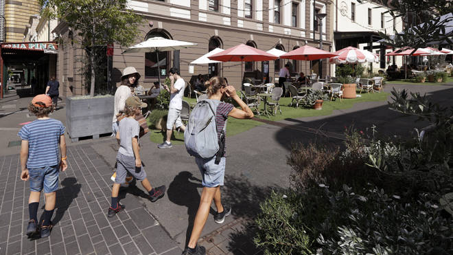 People walk around a popular eating area in Sydney, Australia