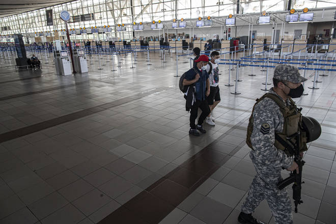 A soldier and a few passengers walk inside the deserted Santiago airport on Monday.