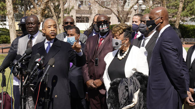 Civil rights activist Rev Al Sharpton, centre, leads a prayer outside the Hennepin County Government Centre during lunch break.