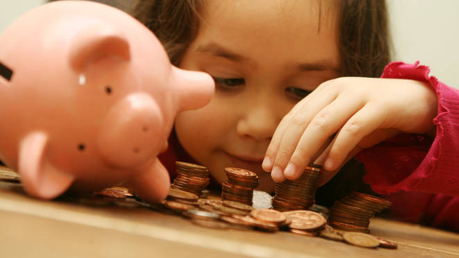 A girl counts the money in her piggy bank