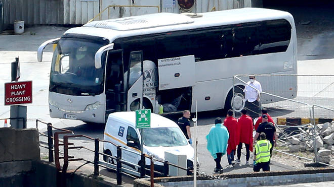 Border Force officers escort men thought to be migrants to a waiting bus in Dover (file image)