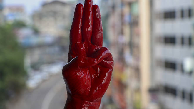 An anti-coup protester shows the three fingered salute of resistance on his red painted hand in memory of protesters who lost their lives (AP)