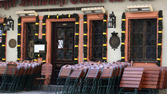 Chairs and tables outside a traditional Bavarian restaurant are locked at the city centre in Munich, Germany (Matthias Schrader/AP)