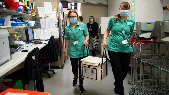 Pharmacists transport a cooler containing the Moderna vaccine, at the West Wales General Hospital in Carmarthen