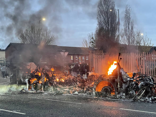 Locals gathered at the remains of a burnt out bus on the Shankill Road, Belfast, on Thursday