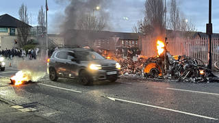 A car drives past a bus that was set on fire amid disorder in Northern Ireland