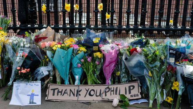 A bouquets of flowers with a note is seen outside Buckingham Palace