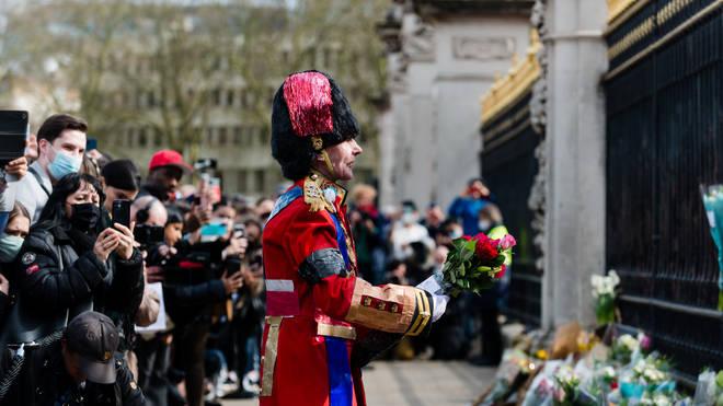 A man speaks and gestures as he brings flowers to Buckingham Palace
