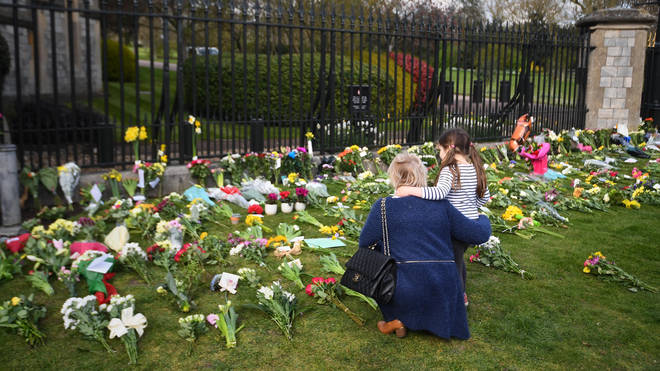 A mother and daughter look at flowers at Cambridge Gate outside Windsor Castle, Berkshire