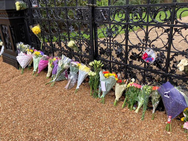 A row of bouquets leans against the gate outside the Sandringham Estate