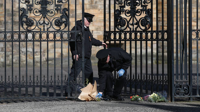 Floral tributes are left at the gates of the Palace of Holyroodhouse, Edinburgh