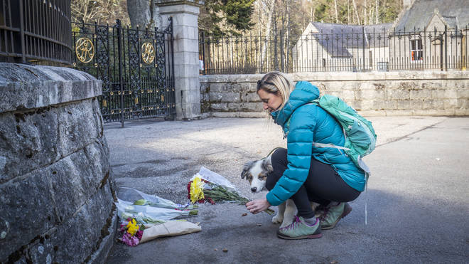 A woman, with dog, lays flowers at the gates of Balmoral Castle in Royal Deeside