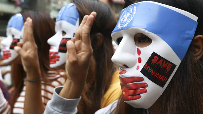 Young demonstrators flash the three-fingered symbol of resistance during an anti-coup mask strike in Yangon, Myanmar