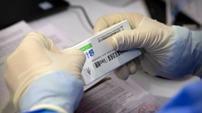 A worker opens a package of coronavirus vaccine made by a Sinopharm subsidiary