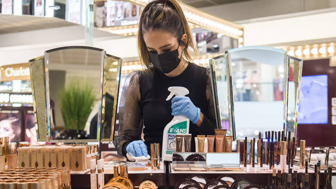 A department store worker cleans products. All non-essential retail can reopen today