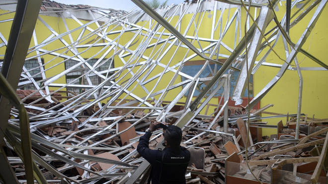 A journalist films earthquake damage to a school in Malang, East Java