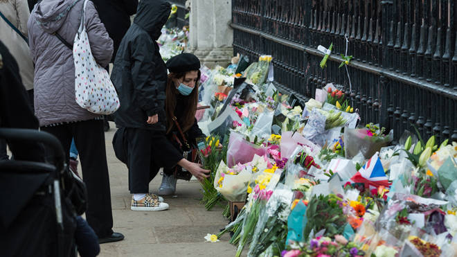 Members of the public lay flowers at Buckingham Palace